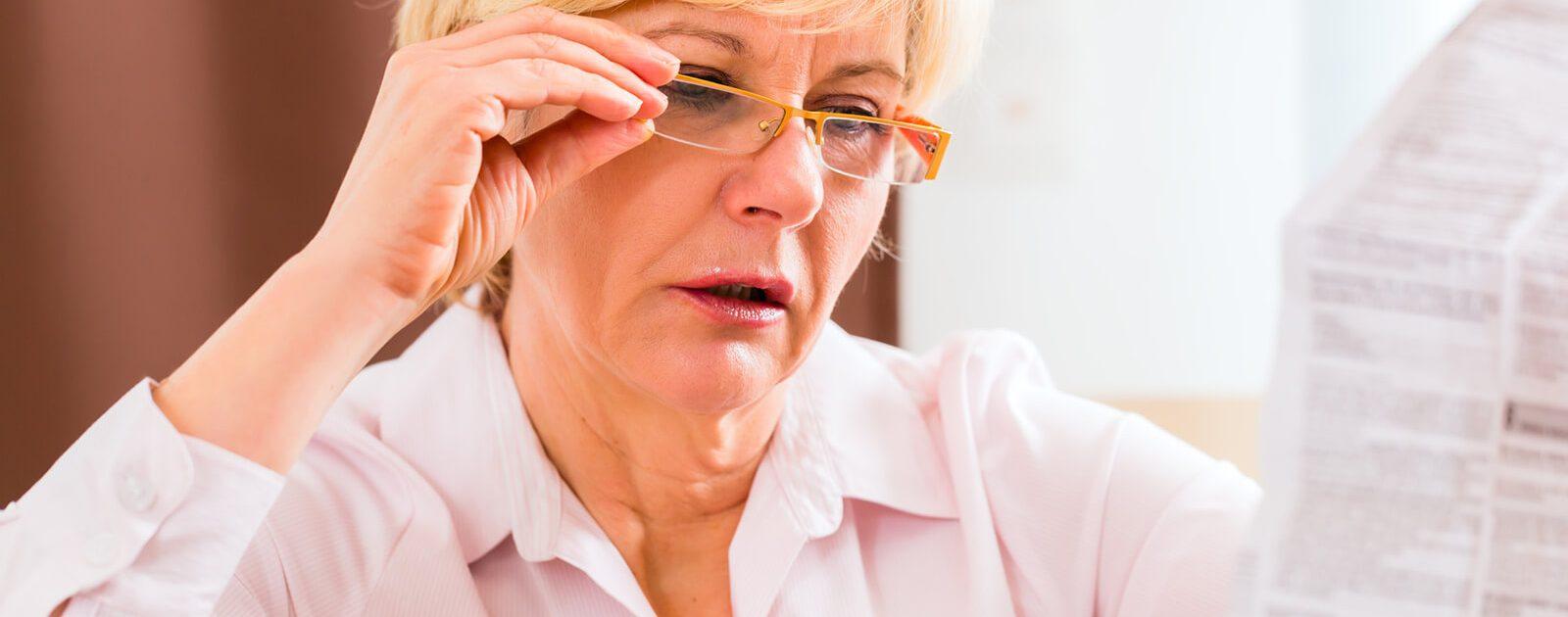 Frau mit Altersweitsichtigkeit (Presbyopie): Nahe Objekte verschwimmen mit zunehmendem Alter