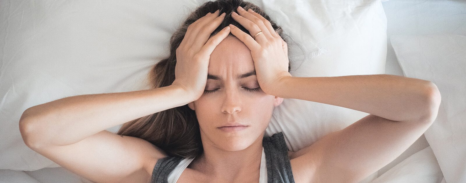Frau liegt mit Augenmigräne im Bett.