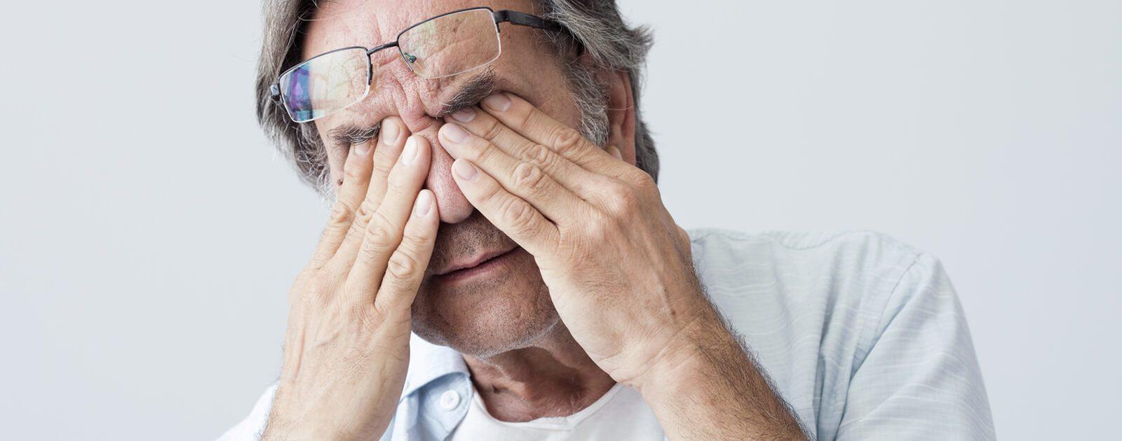 Mann mit Augenverletzung hält ihre Augen zu.