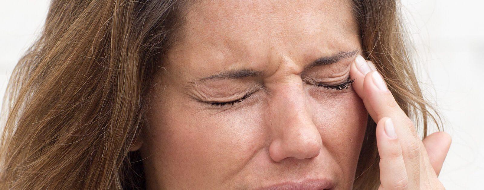 Stechen und Druck im Auge: Frau mit Schmerzen im Auge