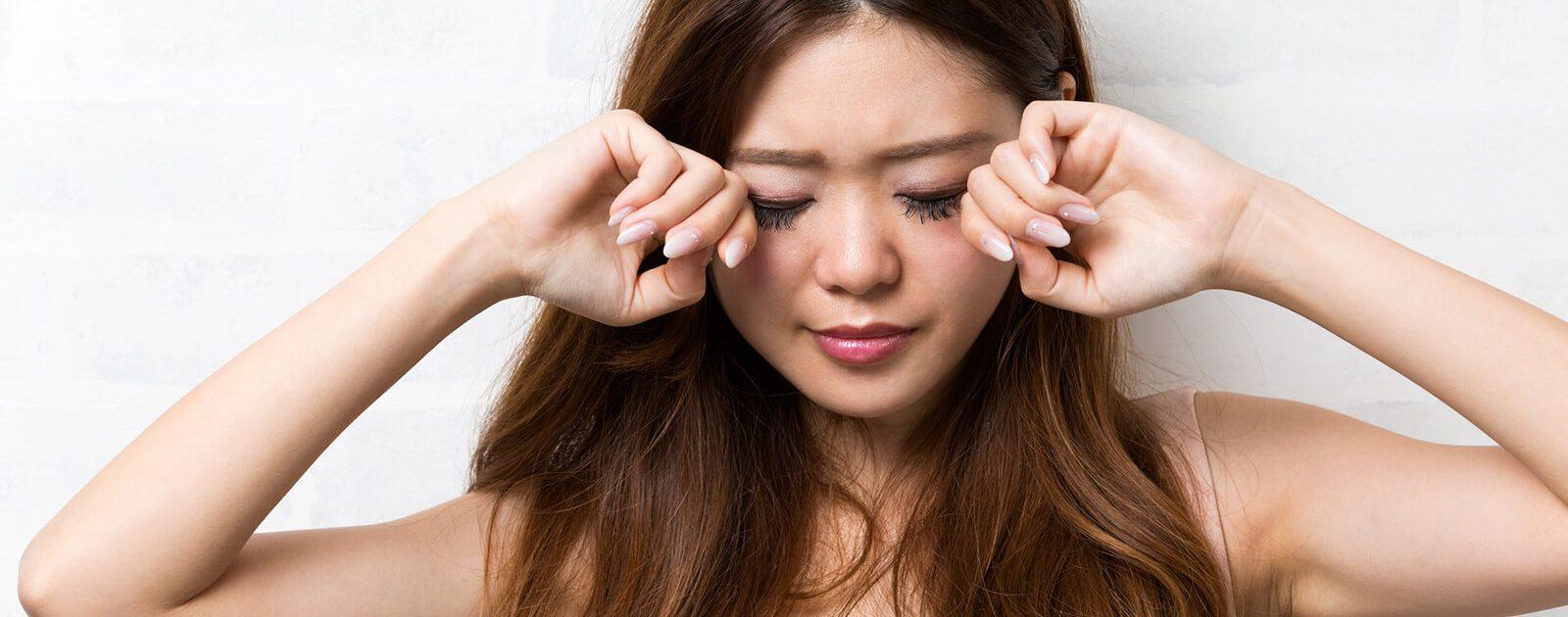 Juckende Augen: Frau reibt sich über geschlossene Augen.