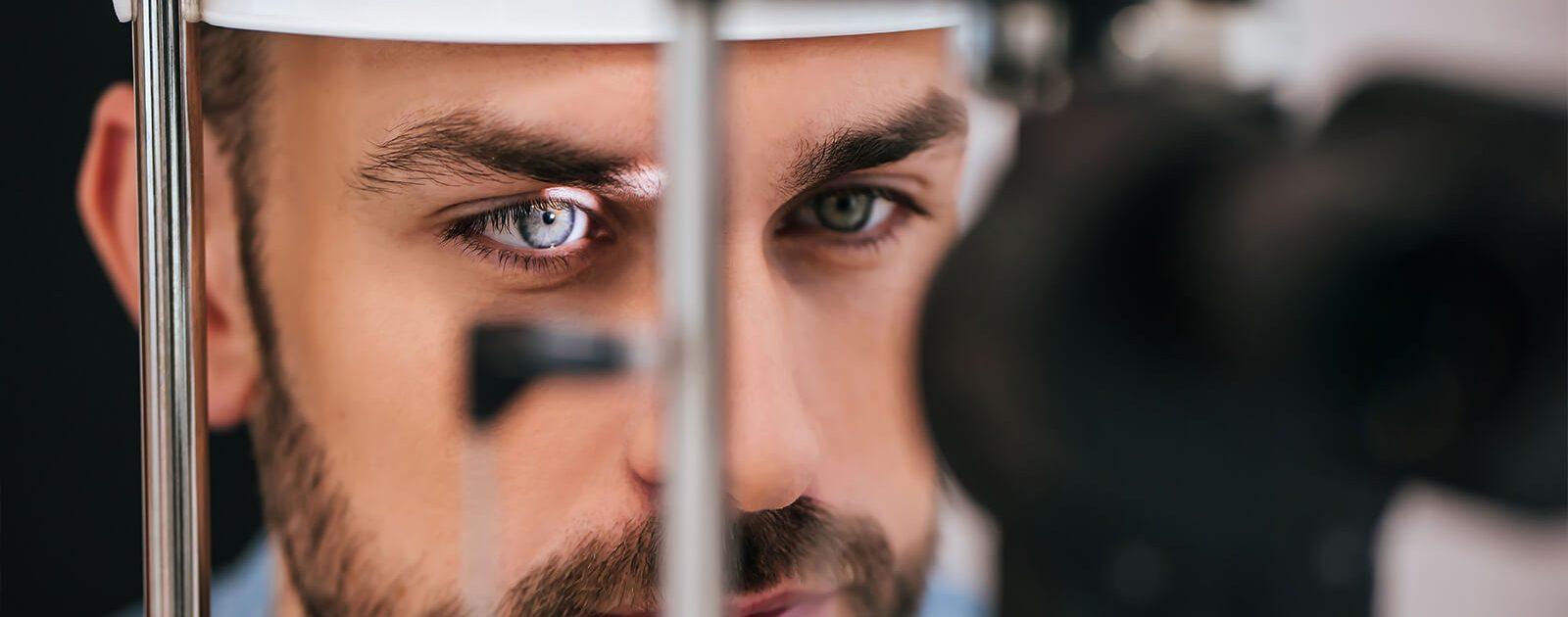 Bei einem Mann wird mithilfe eines speziellen Untersuchungsinstruments eine Netzhautablösung diagnostiziert.