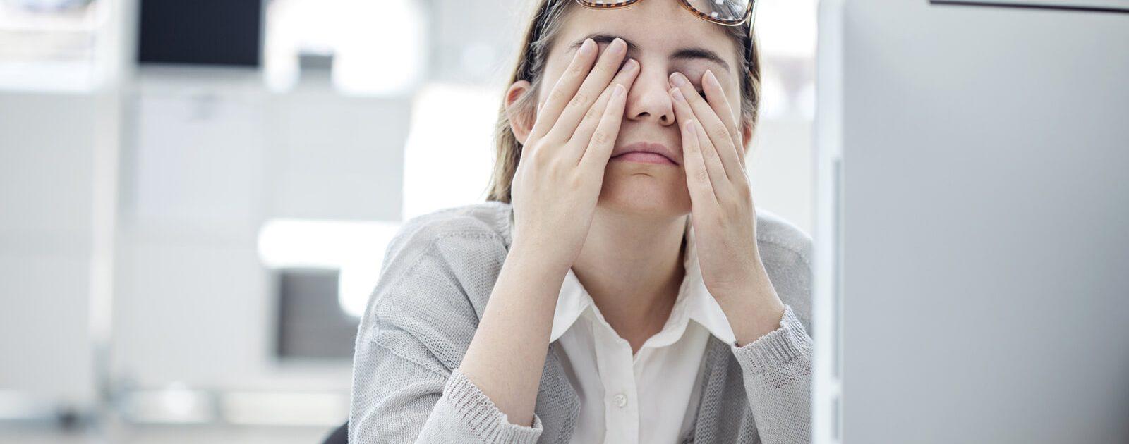 """Frau reibt sich aufgrund des """"Office-Eye-Syndroms"""" die Augen."""