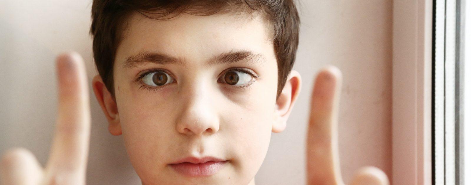 Ein Junge, der schielt – Schielen bei Kindern sollte ernst genommen werden, um Sehbehinderungen zu vermeiden.