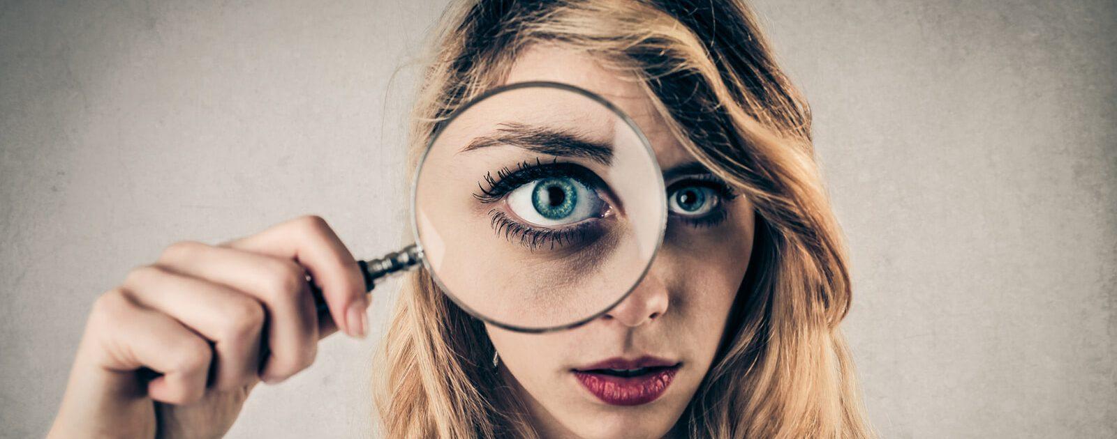 Frau untersucht mit einer Lupe die Symptome von Augenschwerden