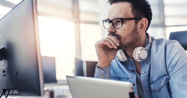 Mann arbeitet am PC — durch VitroCap®N können die Beschwerden seiner Glaskörpertrübung gelindert werden.