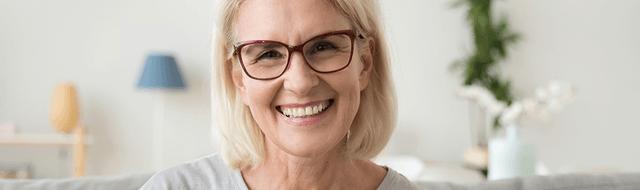 Frau mit Brille lacht, da sie trotz Makuladegeneration dank der Sehhilfe wieder gut sehen kann.