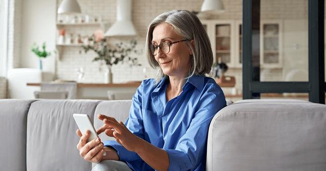 Frau mit AMD nutzt ihr Smartphone als elektronisches Hilfsmittel gegen ihre Sehschwäche.